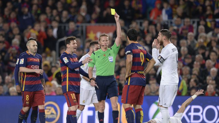 Barcelona's Uruguayan forward Luis Suarez (2R) is handed a yellow card