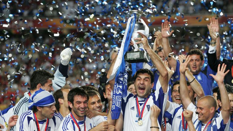 LISBON, PORTUGAL - JULY 4:  Traianos Dellas of Greece lifts the trophy during the UEFA Euro 2004 Final match
