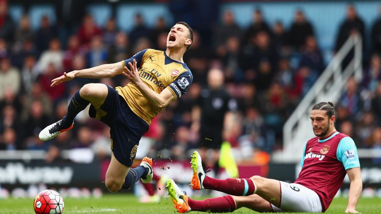 Laurent Koscielny of Arsenal is tackled by Andy Carroll of West Ham United during the Barclays Premier League match between Arsenal and West Ham