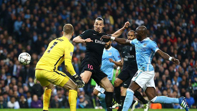 Zlatan Ibrahimovic of Paris Saint-Germain beats Eliaquim Mangala (20) and Joe Hart of Manchester City to score, but his goal is disallowed