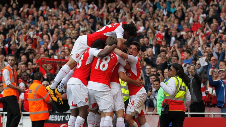 Arsenal players mob Arsenal's Spanish midfielder Mikel Arteta as he celebrates scoring his team's fourth goal during the English Premier League football ma