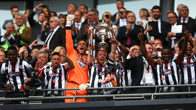 Grimsby's Craig Disley lifts the Vanarama National League play-off trophy