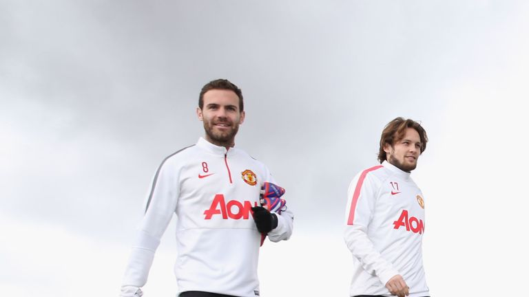 Juan Mata and Daley Blind of Manchester United walk out ahead of a first team training session at Aon Training Complex