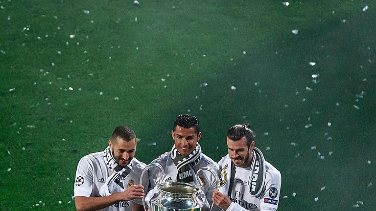 MADRID, SPAIN - MAY 29: Cristiano Ronaldo (2ndL) of Real Madrid CF holds the trophy as he poses for a picture with his teammates Karim Benzema (L) and Gare