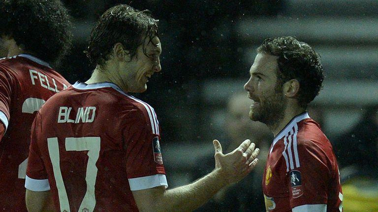 Manchester United's Dutch midfielder Daley Blind (L) congratulates Manchester United's Spanish midfielder Juan Mata
