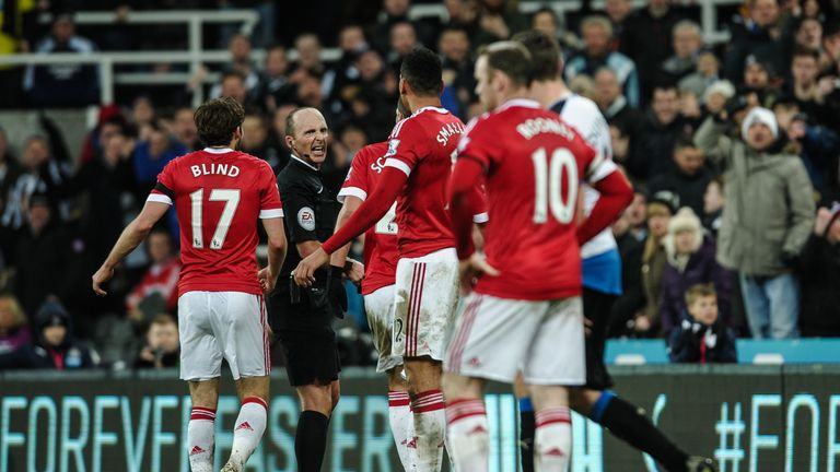 NEWCASTLE, ENGLAND - JANUARY 12:  Referee Mike Dean (second from left) reacts as Manchester player surround him  during the Barclays Premier League match b