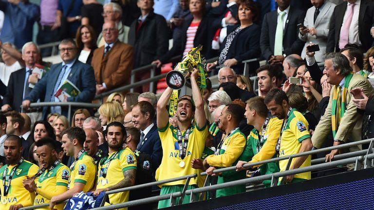 Norwich City's Scottish defender Steven Whittaker (C) raises the trophy