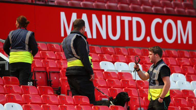 A sniffer dog patrols the stands as Man Utd v Bournemouth is abandoned with fans evacuated from Old Trafford