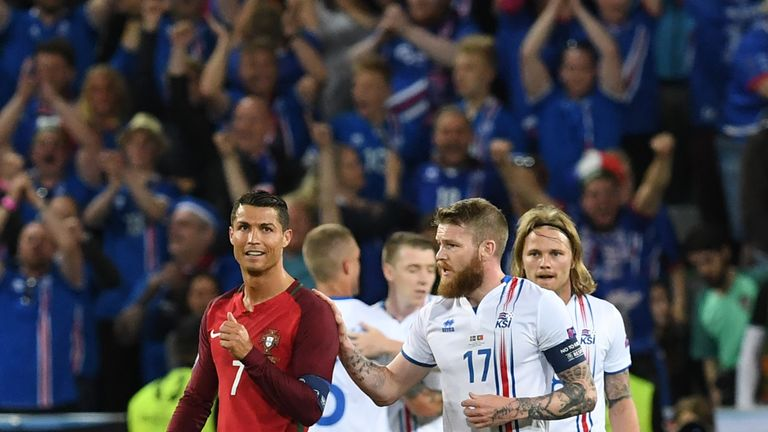 Iceland's midfielder Aron Gunnarsson (R) taps Portugal's forward Cristiano Ronaldo (L) on the shoulder at the end of the Euro 2016 group F football match
