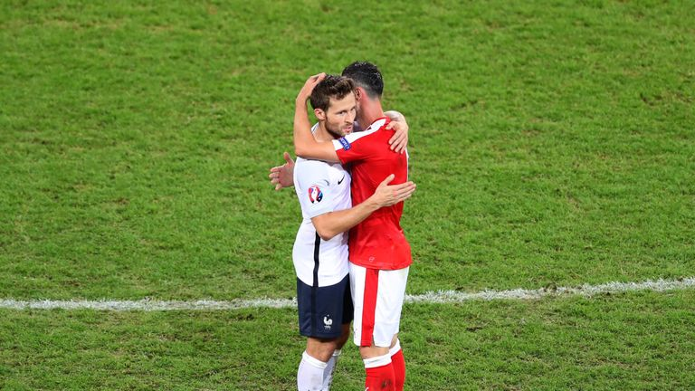 Switzerland's Blerim Dzemaili and France's Yohan Cabaye hug each other at full time