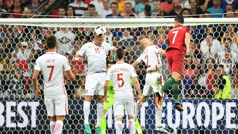 Cristiano Ronaldo (R) jumps for the ball with Poland's defender Kamil Glik (2L)