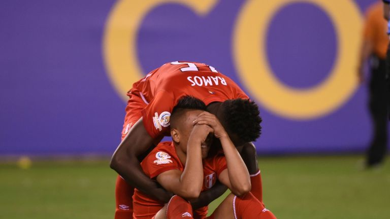 Peru's Christian Cueva (sitting) is comforted by teammate Christian Ramos as he cries inconsolably after missing his shot in the penalty shoot-out
