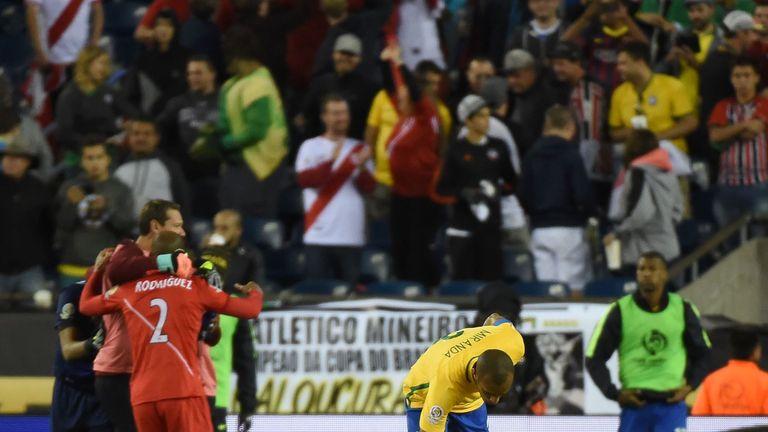Members of Peru's national team celebrate their victory as Brazil's Miranda comforts team-mate Renato Augusto