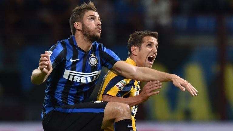 MILAN, ITALY - SEPTEMBER 23:  Davide Santon (L) of Internazionale Milano and Juan Gomez of Hellas Verona compete for the ball during the Serie A match betw