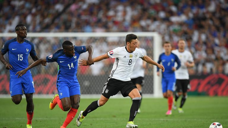Mesut Oezil of Germany runs with the ball under pressure from Blaise Matuidi of France during the UEFA EURO semi final match