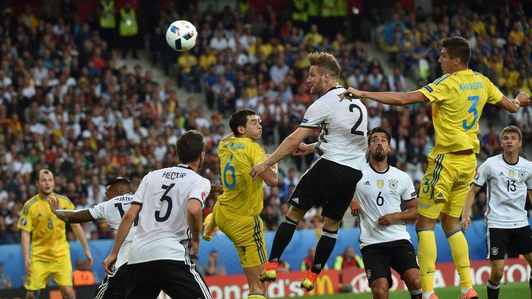 Germany's defender Shkodran Mustafi (2nd-R) jumps to head the ball between Ukraine's midfielder Taras Stepanenko (C) and Ukraine's defender Yevhen Khacheri