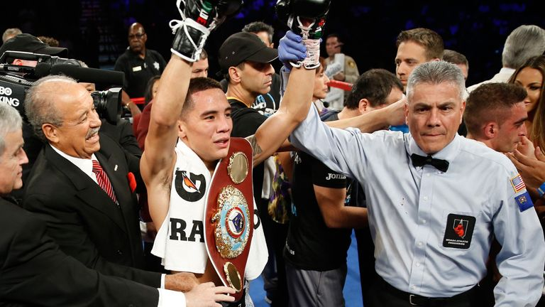 Oscar Valdez Jr. (C) of Mexico poses with the referee Russell Mora after defeating Matias Rueda of Argentina