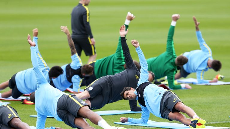 Manchester City's Jesus Navas (facing camera) joins in strength-building exercises during a training session at City Football Academy