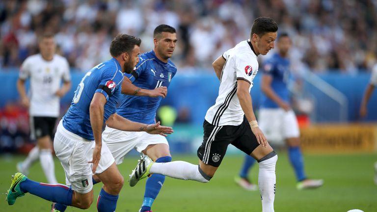 Germany's Mesut Ozil (right) holds off a challenge from Italy's Antonio Candreva and Italy's Stefano Sturaro (centree)