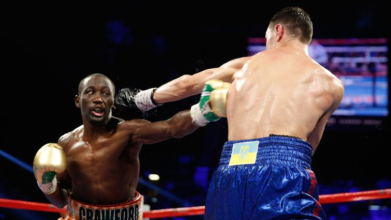 LAS VEGAS, NV - JULY 23:  WBO junior welterweight champion Terence Crawford (L) lands a body shot on WBC champion Viktor Postol of Ukraine
