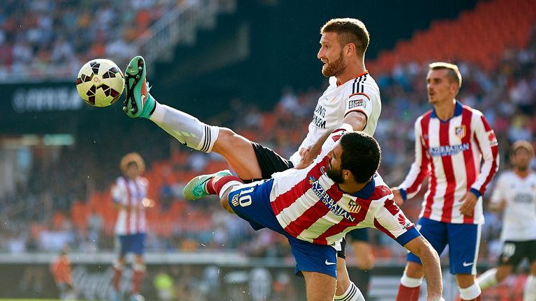 VALENCIA, SPAIN - OCTOBER 04:  Arda Turan (R) of Atletico de Madrid is tackled by Shkodran Mustafi of Valencia during the La Liga match between Valencia CF