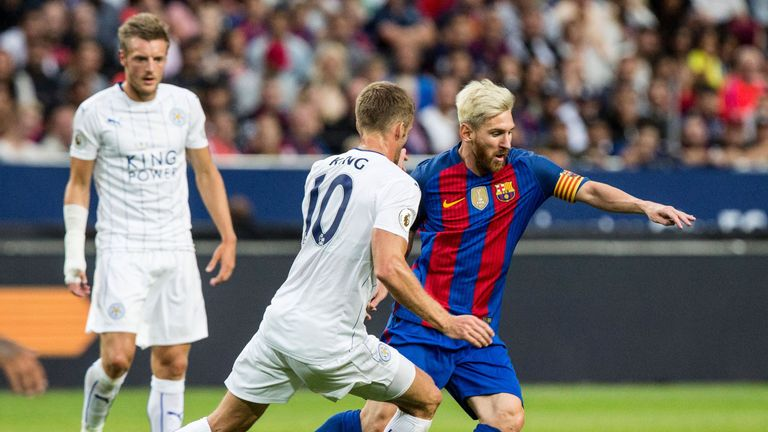 Leicester's Andy King (C) challenges Barcelona's Lionel Messi during the 2016 International Champions Cup friendly football match between FC Barcelona and