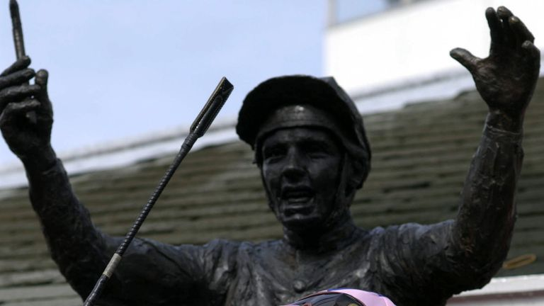 Frankie Dettori stands in front of a statue to comemerate his seven wins on one day at Ascot
