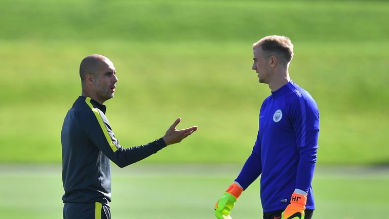 Manchester City manager Pep Guardiola talks to goalkeeper Joe Hart during a training session at the City Football Academy, Manchester.