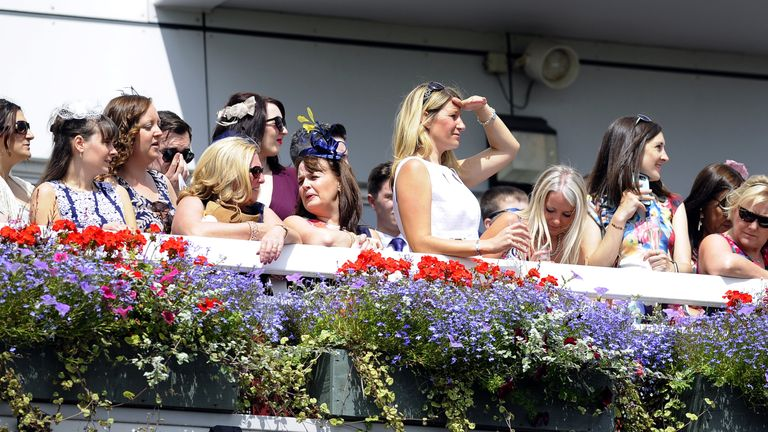 Racegoers watch the action during Betfred Rose Of Lancaster Stakes at Haydock Park Racecourse.