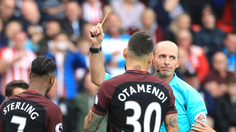 Referee Mike Dean (R) shows Raheem Sterling (L) a yellow card after awarding Stoke a penalty