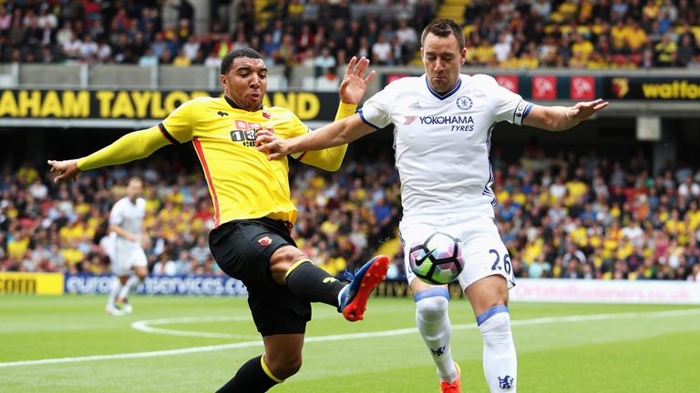 Troy Deeney of Watford stretches to get to the ball before John Terry