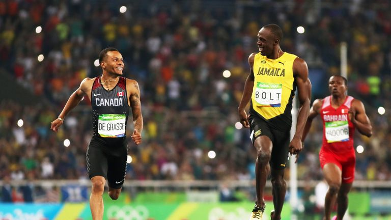 Bolt smiles across at Canada's Andre de Grasse in the 200m semi-final