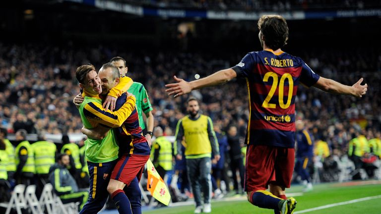 Andres Iniesta celebrates with Lionel Messi after scoring against Real Madrid