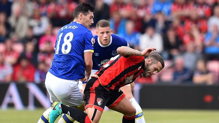 Jack Wilshere (R) vies for possession with Gareth Barry