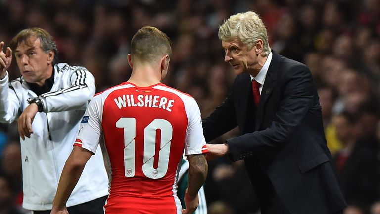 Arsenal's French manager Arsene Wenger (R) gives last minute instructions to Arsenal's English midfielder Jack Wilshere (L) in the dying minutes of the UEF