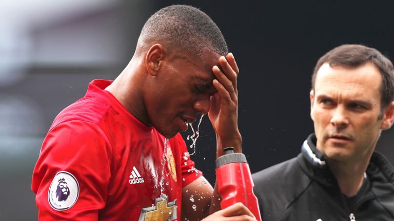 Anthony Martial walks off the pitch with a member of the Manchester United medical team after a clash of heads