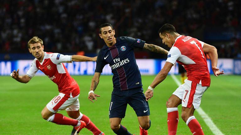 Paris Saint-Germain midfielder Angel Di Maria (C) vies with Arsenal duo Nacho Monreal (L) and Alexis Sanchez (R)