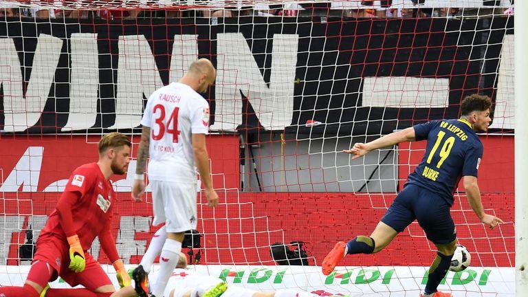 Leipzig's Scottish midfielder Oliver Burke (R) scores the opening goal past Cologne's goalkeeper Timo Horn (L) during the German first division Bundesliga