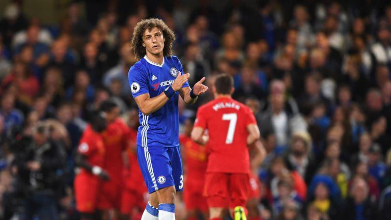 David Luiz reacts as Liverpool players celebrate Dejan Lovren's goal