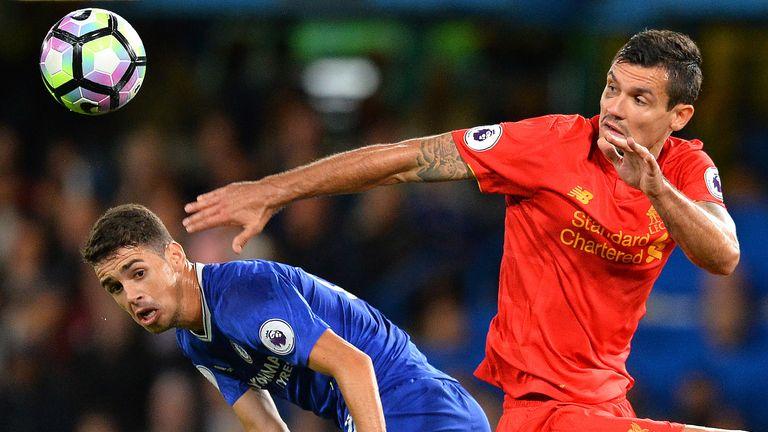Oscar (L) and Dejan Lovren battle for possession