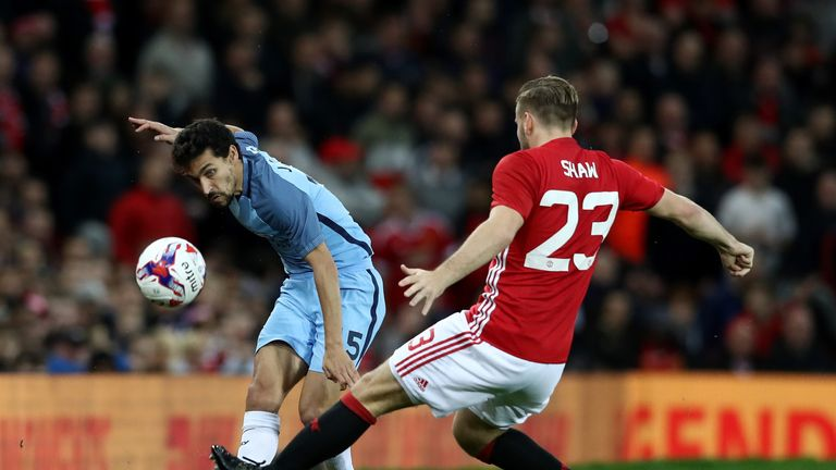 Jesus Navas of Manchester City (L) crosses the ball while Luke Shaw of Manchester United (R) attempts to block during the EFL Cup tie