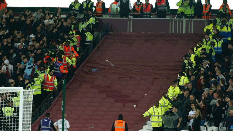 Supporters of both sides confront each other and a seat is seen being thrown during the EFL Cup fourth round match between West Ham and Chelsea