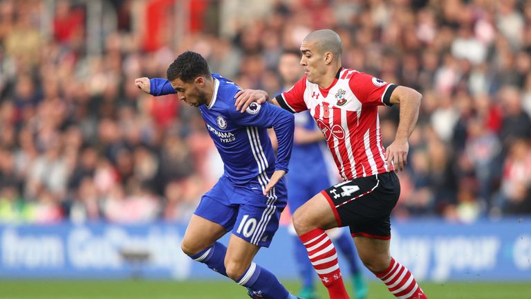 Eden Hazard of Chelsea (L) is challenged by Oriol Romeu of Southampton