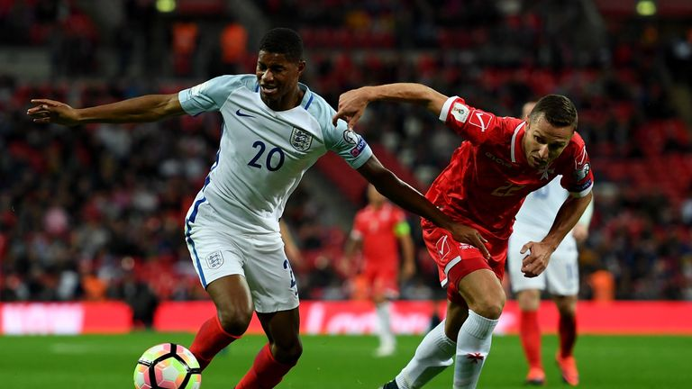 Marcus Rashford holds off pressure from Alex Muscat