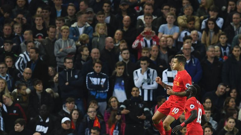 Liverpool's Brazilian midfielder Philippe Coutinho (L) celebrates after scoring