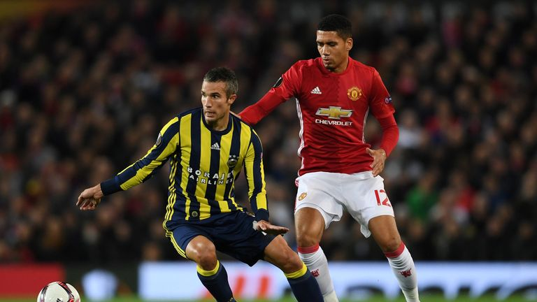 MANCHESTER, ENGLAND - OCTOBER 20:  Robin van Persie of Fenerbahce is closed down by Chris Smalling of Manchester United  during the UEFA Europa League Grou