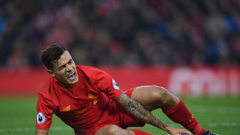 Liverpool's Brazilian midfielder Philippe Coutinho holds his foot as he lies on the pitch injured during the English Premier League football match between