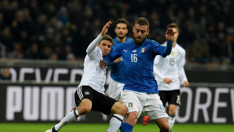 Italy midfielder Daniele De Rossi (right) is tackled by Germany counterpart Thomas Muller