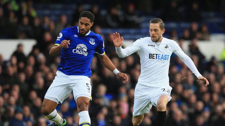 Ashley Williams of Everton (L) is put under pressure from Swansea's Gylfi Sigurdsson