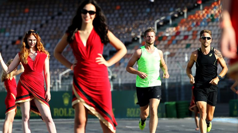 Jenson Button runs past the German GP grid girls as they practice the night before race day - Picture from Getty Images